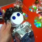 A robot made with a medium size foil box, ice cream cup and some shredded pieces of tapes.